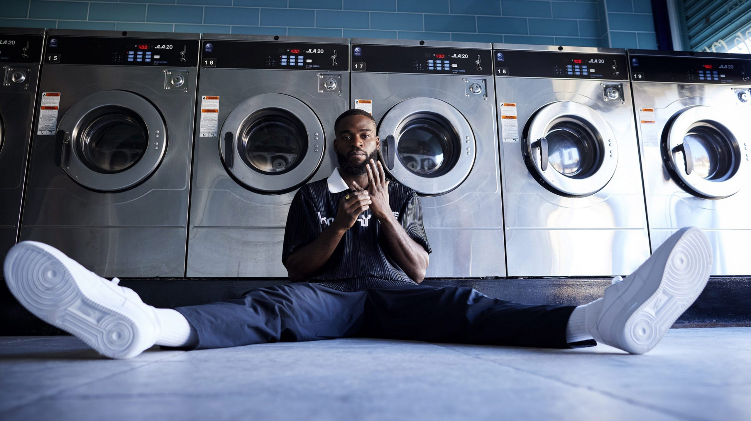 Joshua Buatsi sat on the floor with his legs out wide under some clothes washing machines