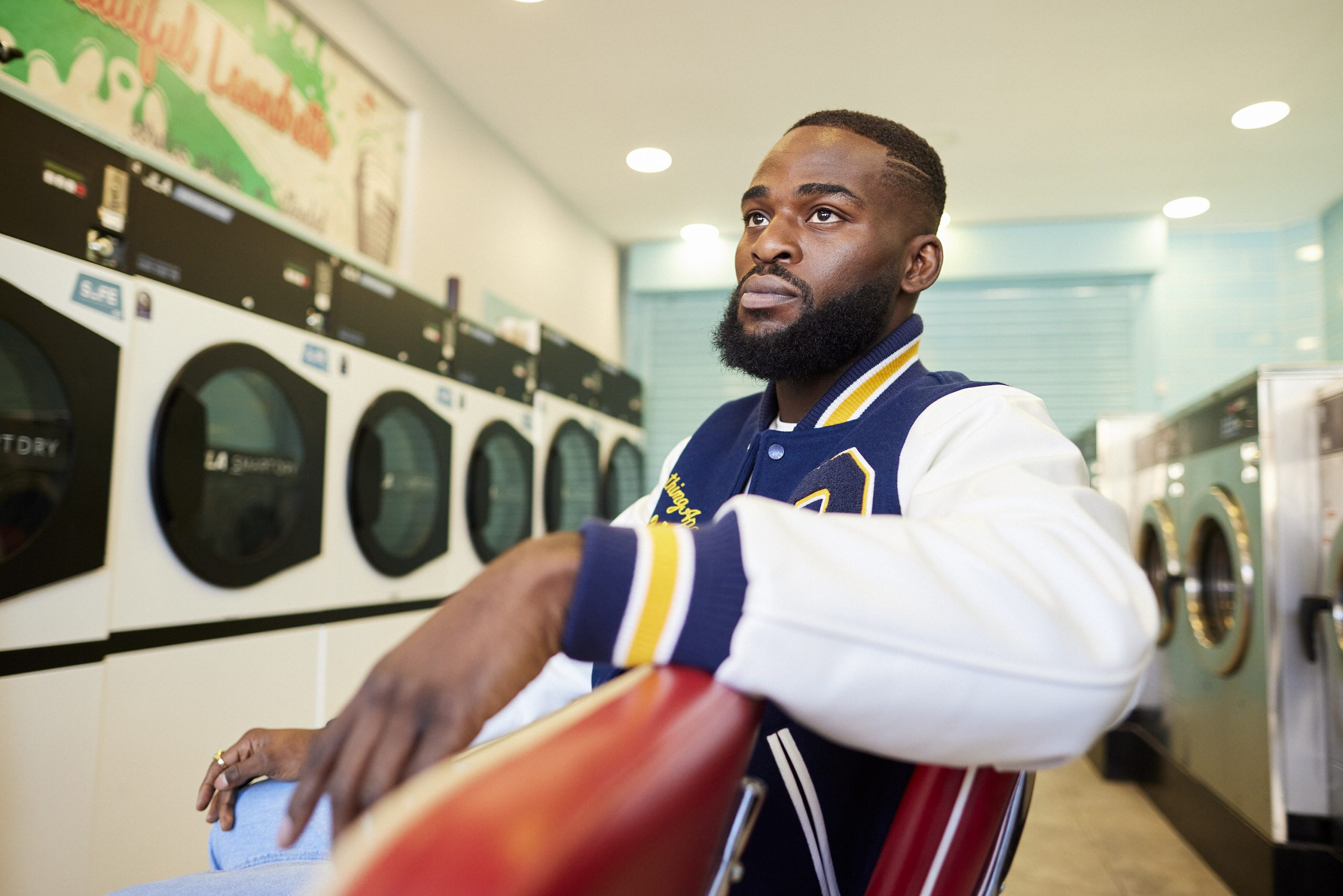 Joshua Buatsi sat on some red plastic chairs in a laundromat