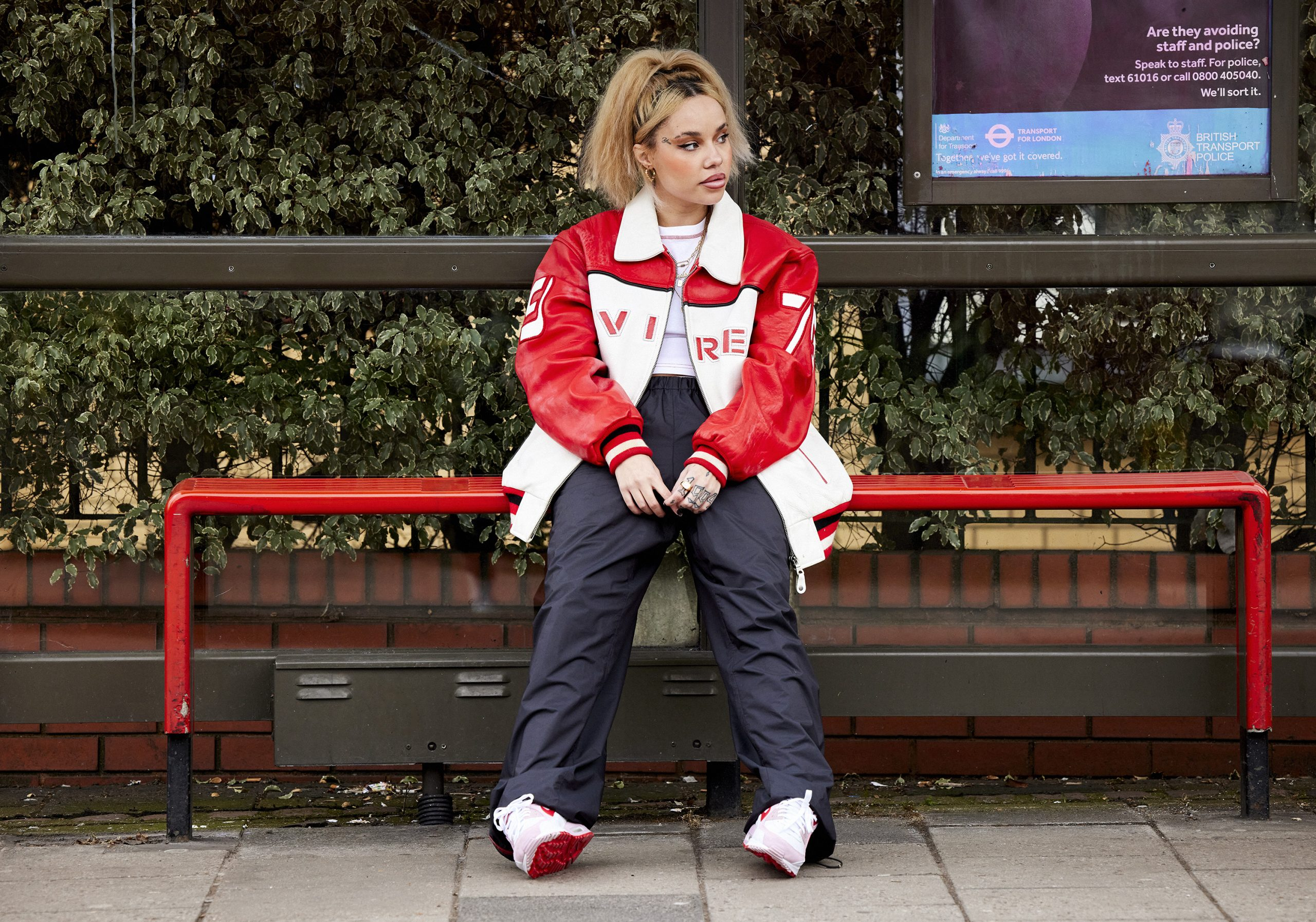 JGRREY sitting at a bus stop on a red bench