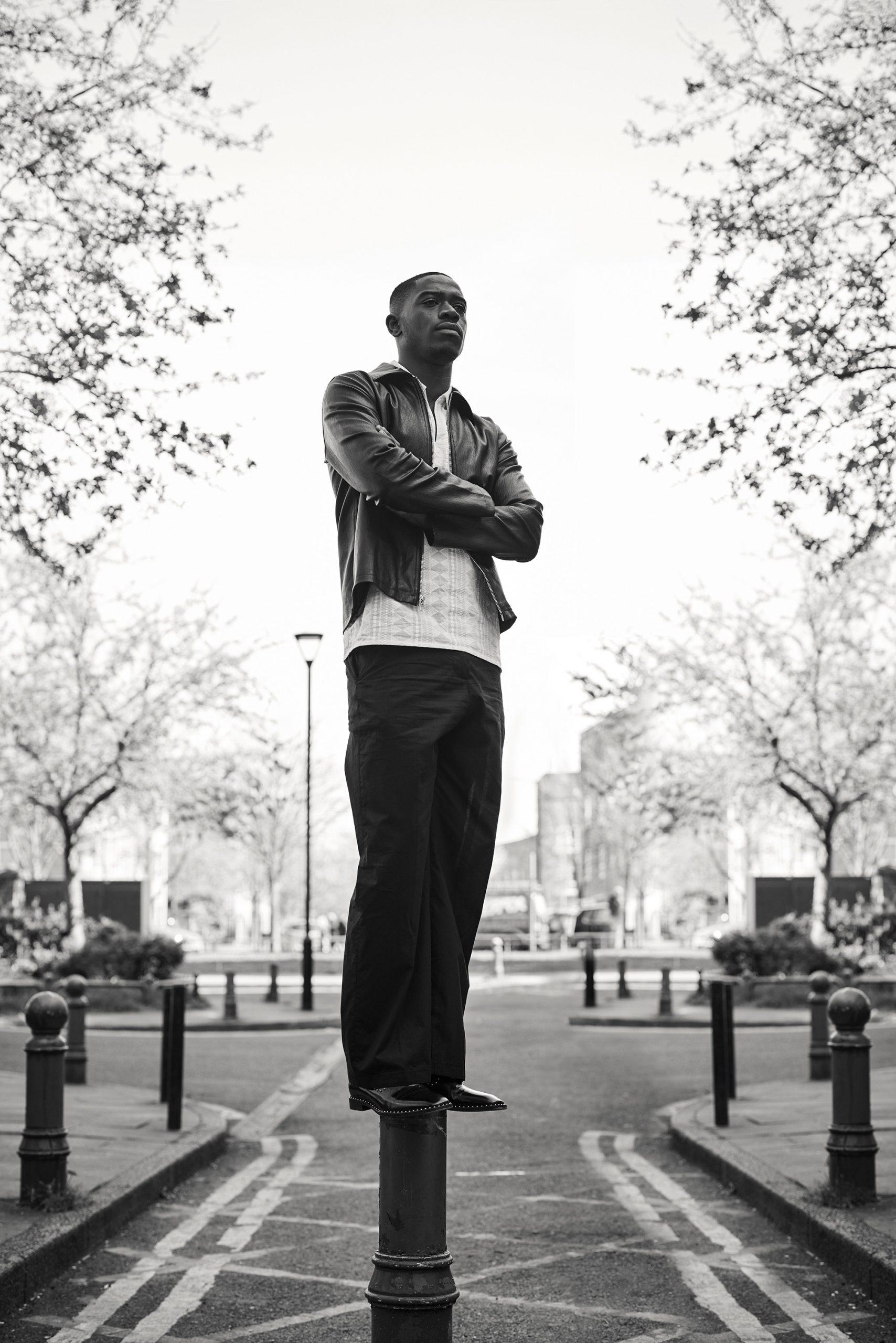 Damson Idris stood on a bollard with his arms crossed