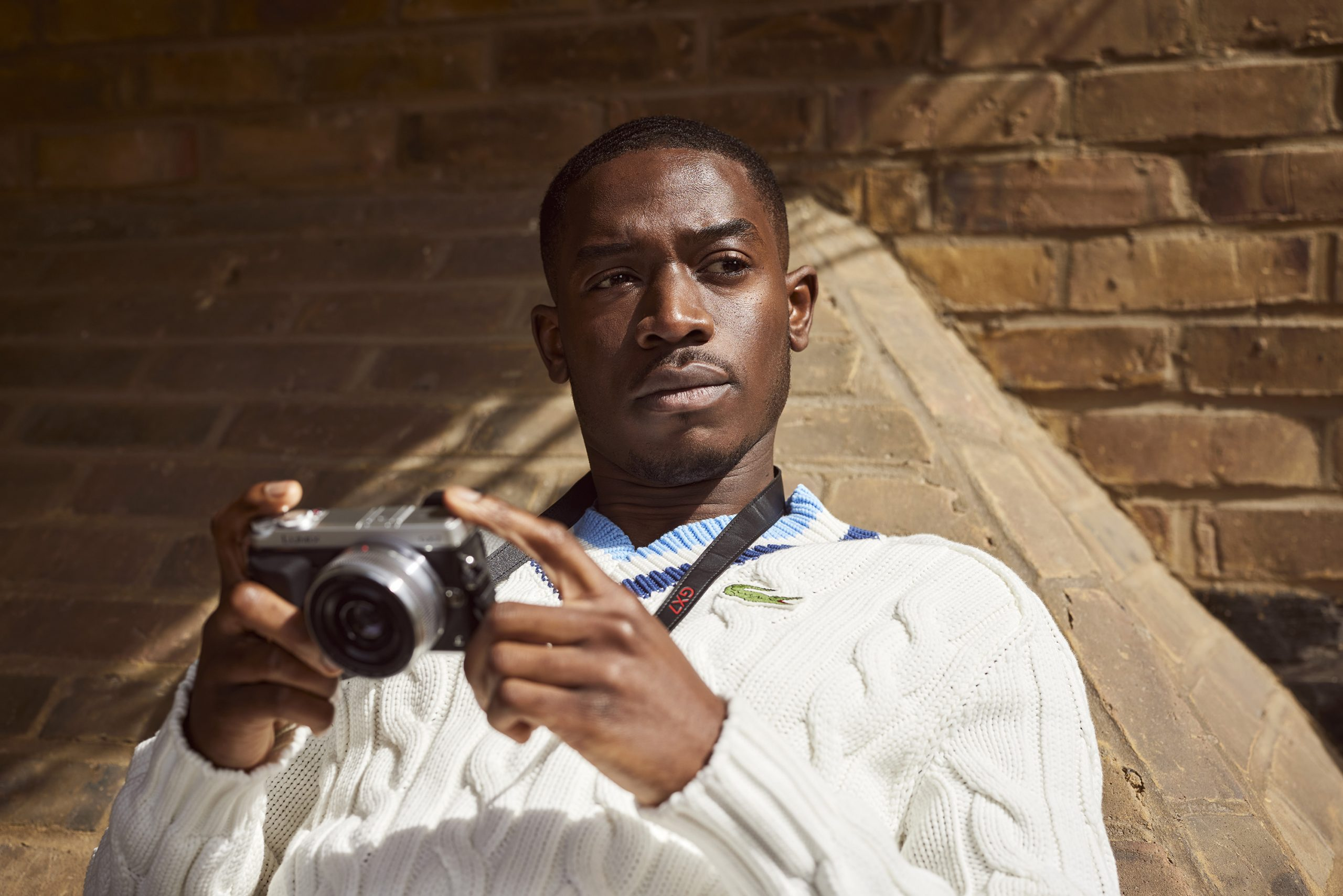Damson Idris holding a camera while leaning on a brick wall