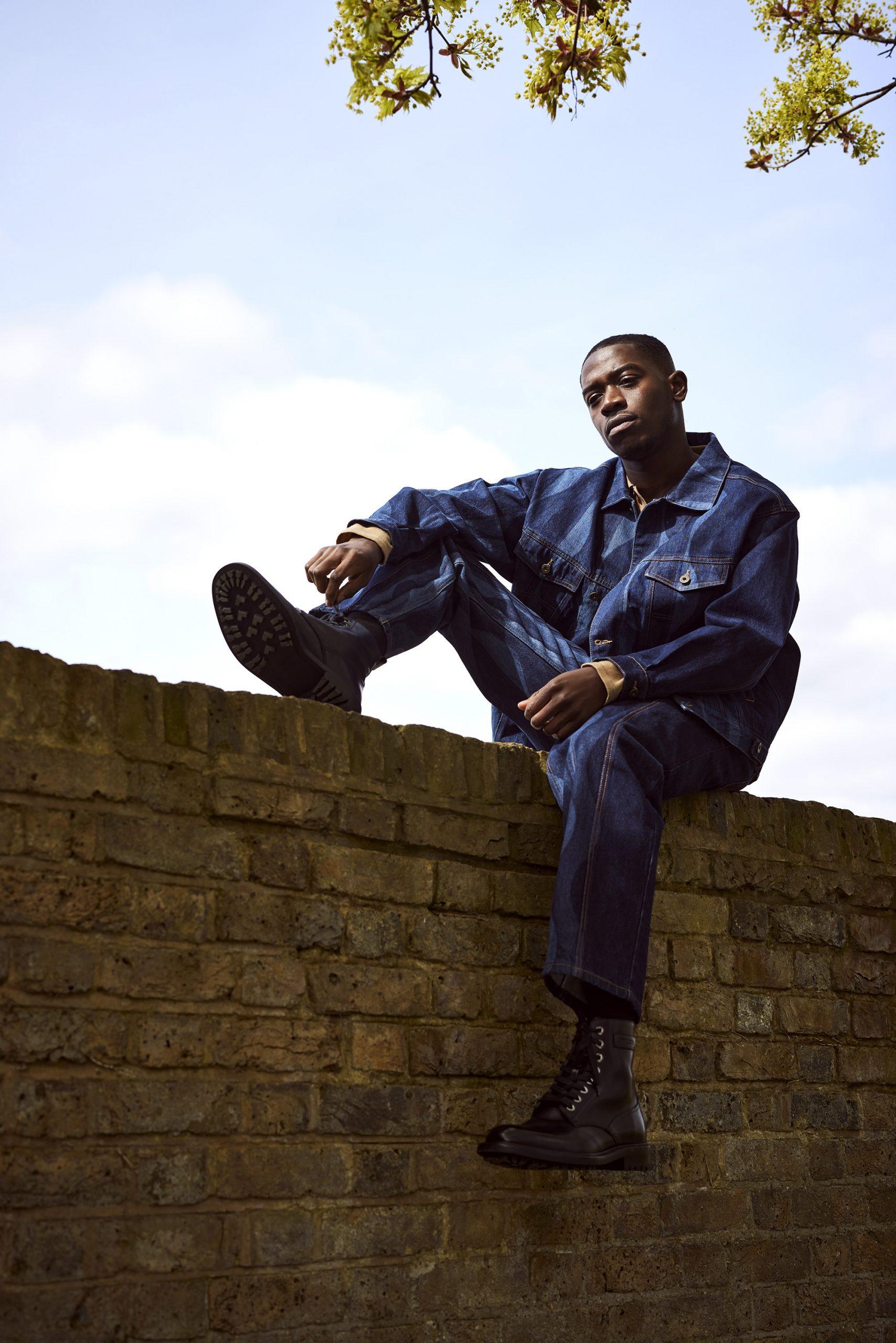 Damson Idris sat on a brick wall wearing a denim jacket and trousers