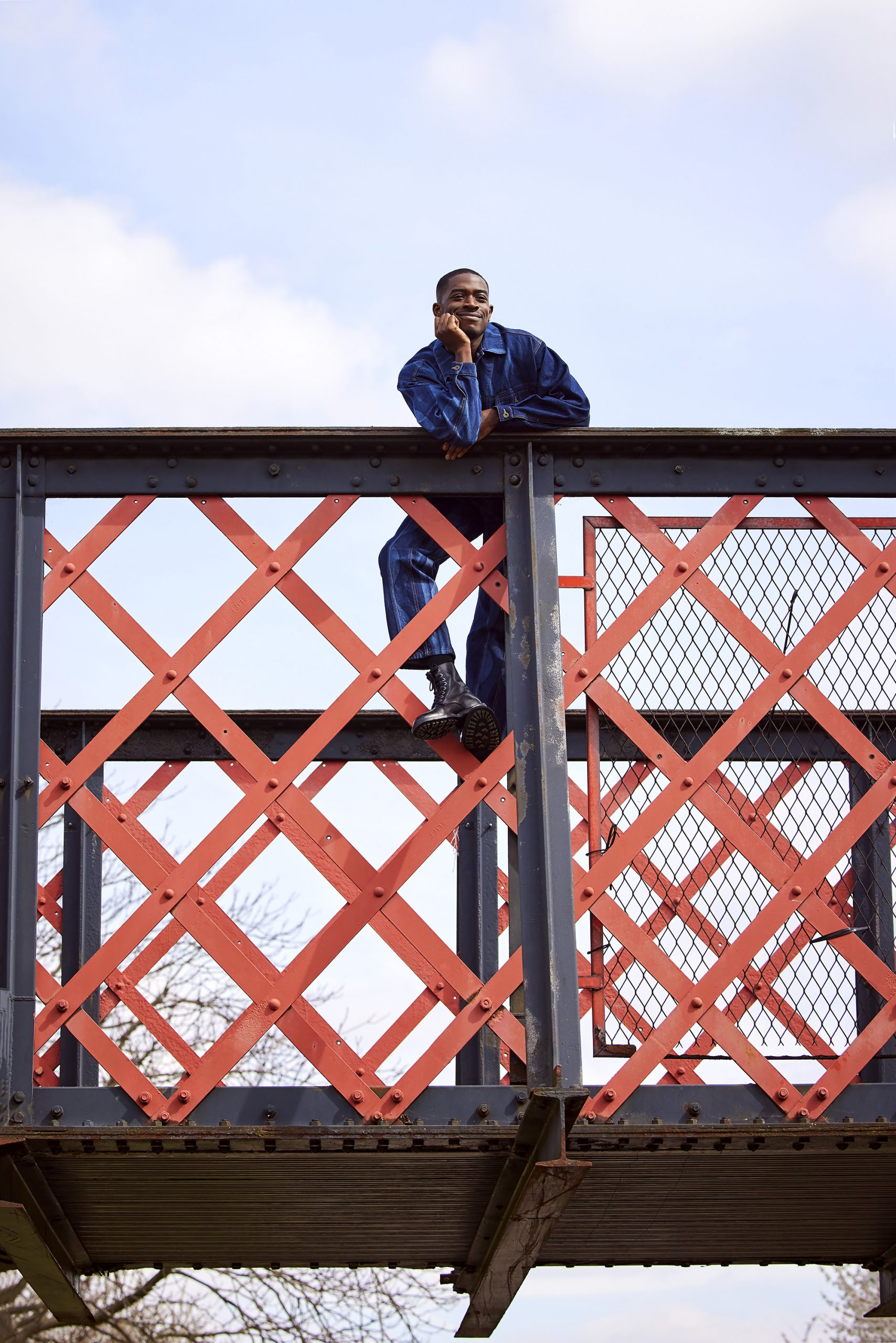 Damson Idris climbing up the metal railings on a bridge with his chin on his hand, smiling
