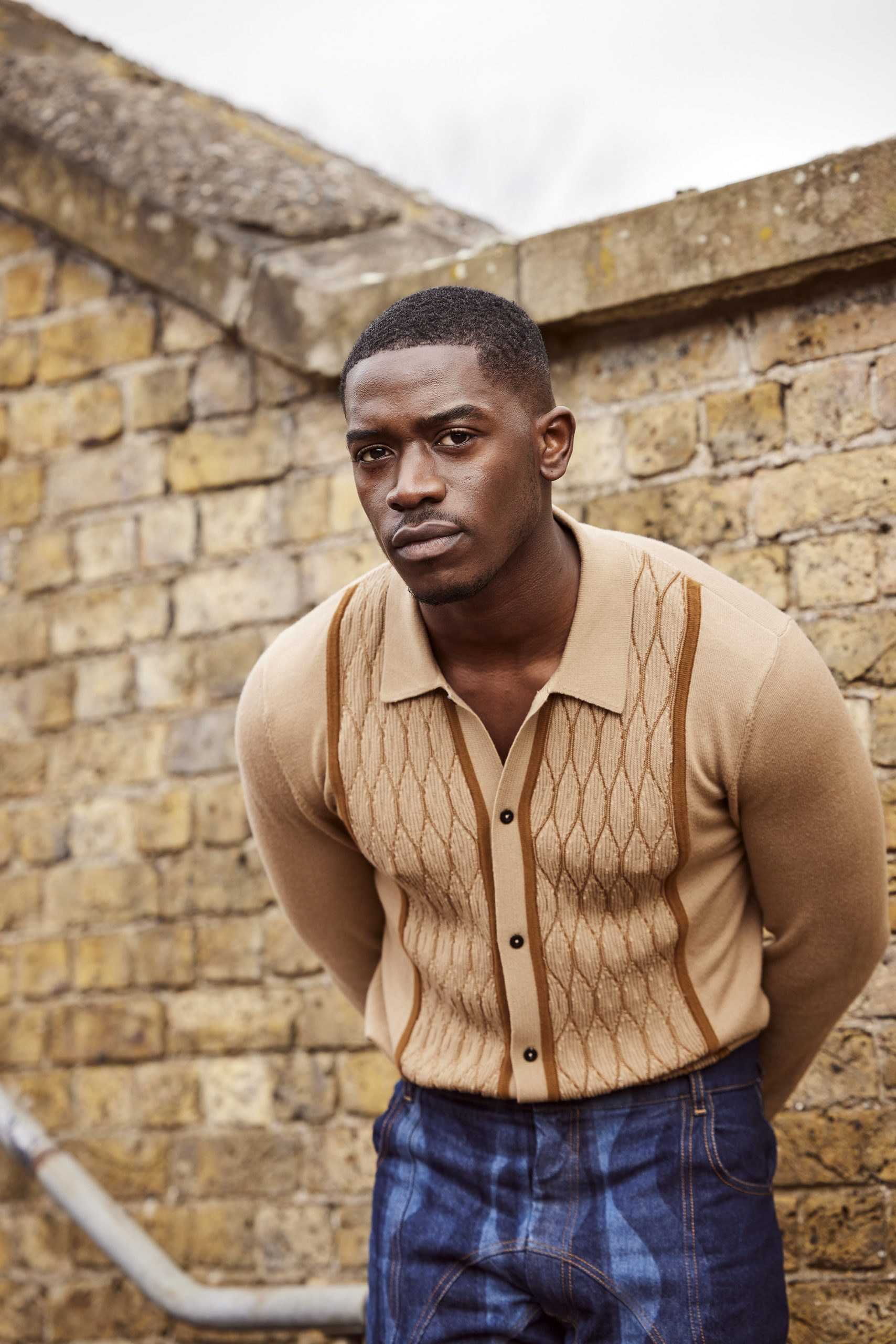 Damson Idris stood on stairway and looking at the camera