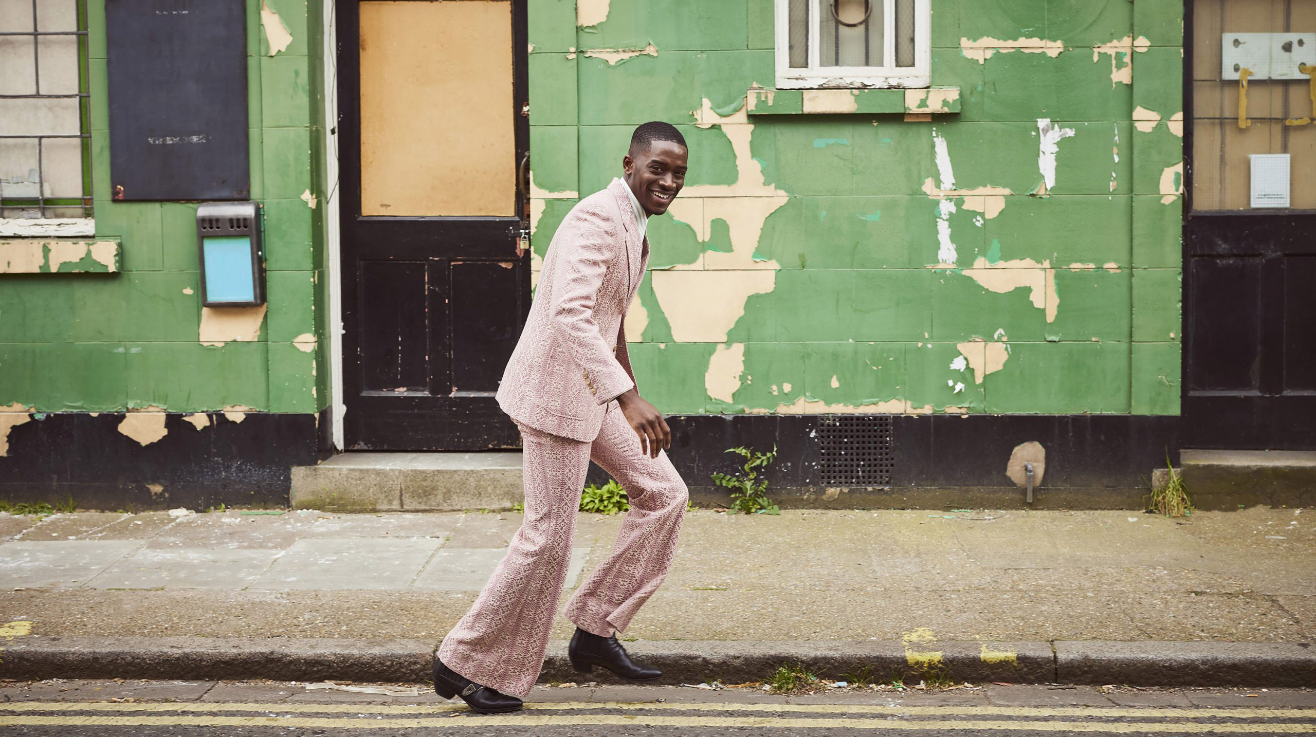 Damson Idris smiling while walking on the road by a flaking green painted wall