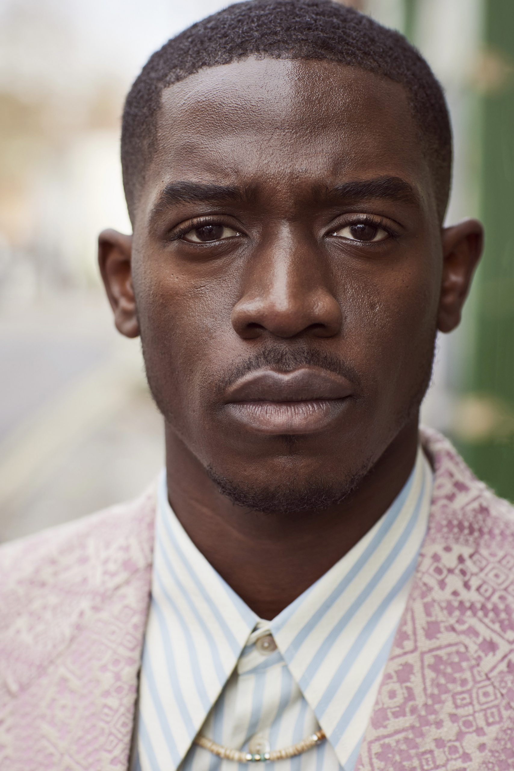 Damson Idris looking at the camera wearing a blue and white striped shirt