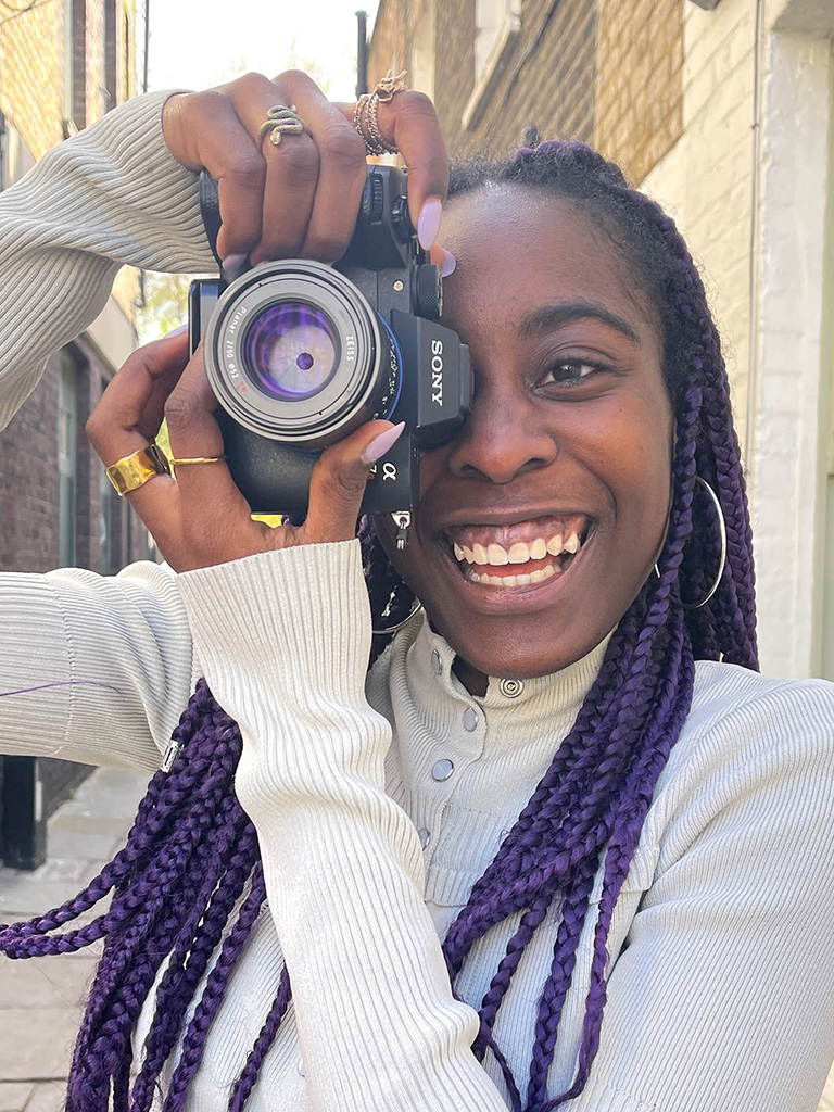 Lara Soluade holding a camera smiling