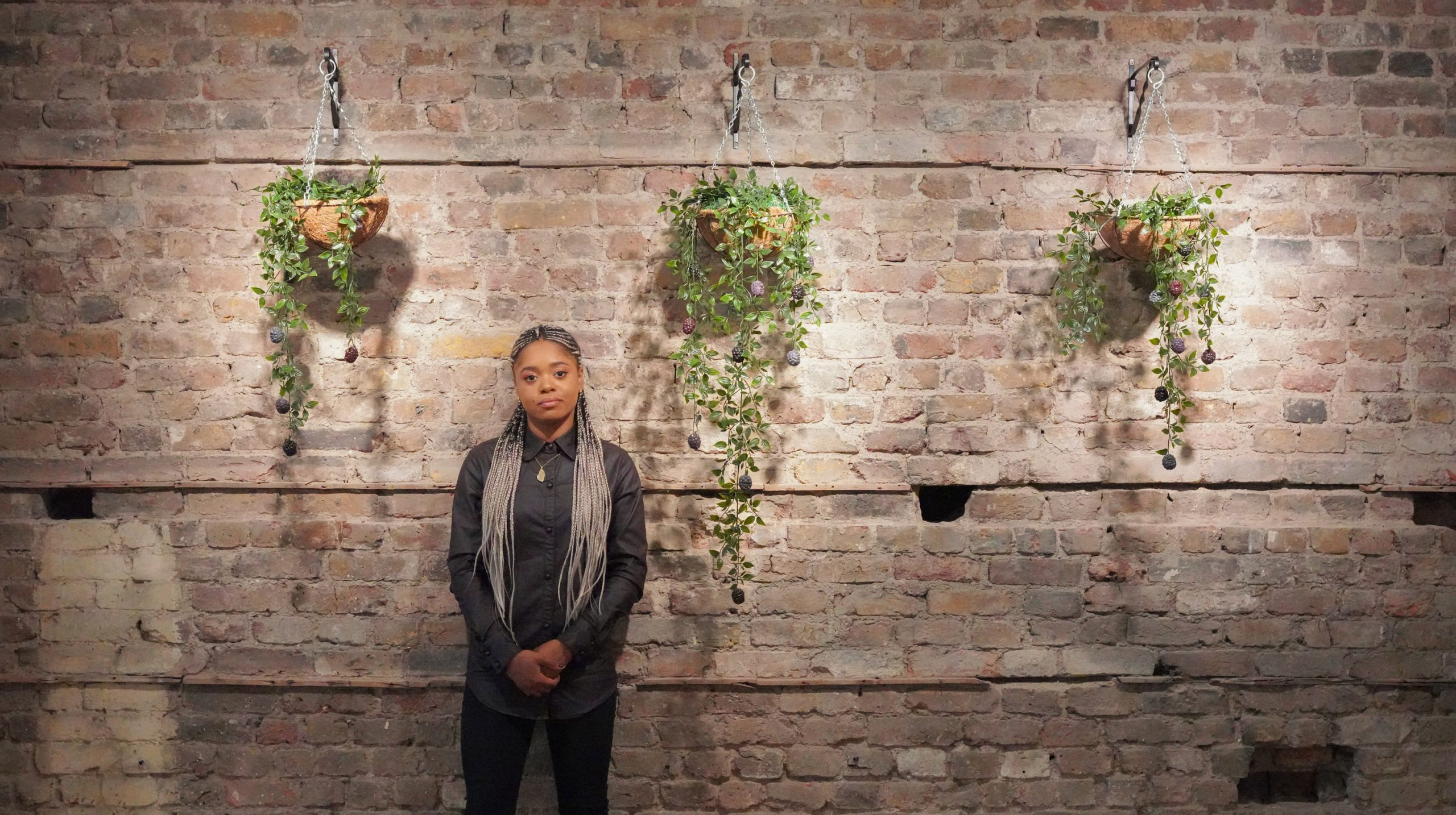 Lauren Marie Haywood beside some of her handmade plant artwork mounted on a brick wall