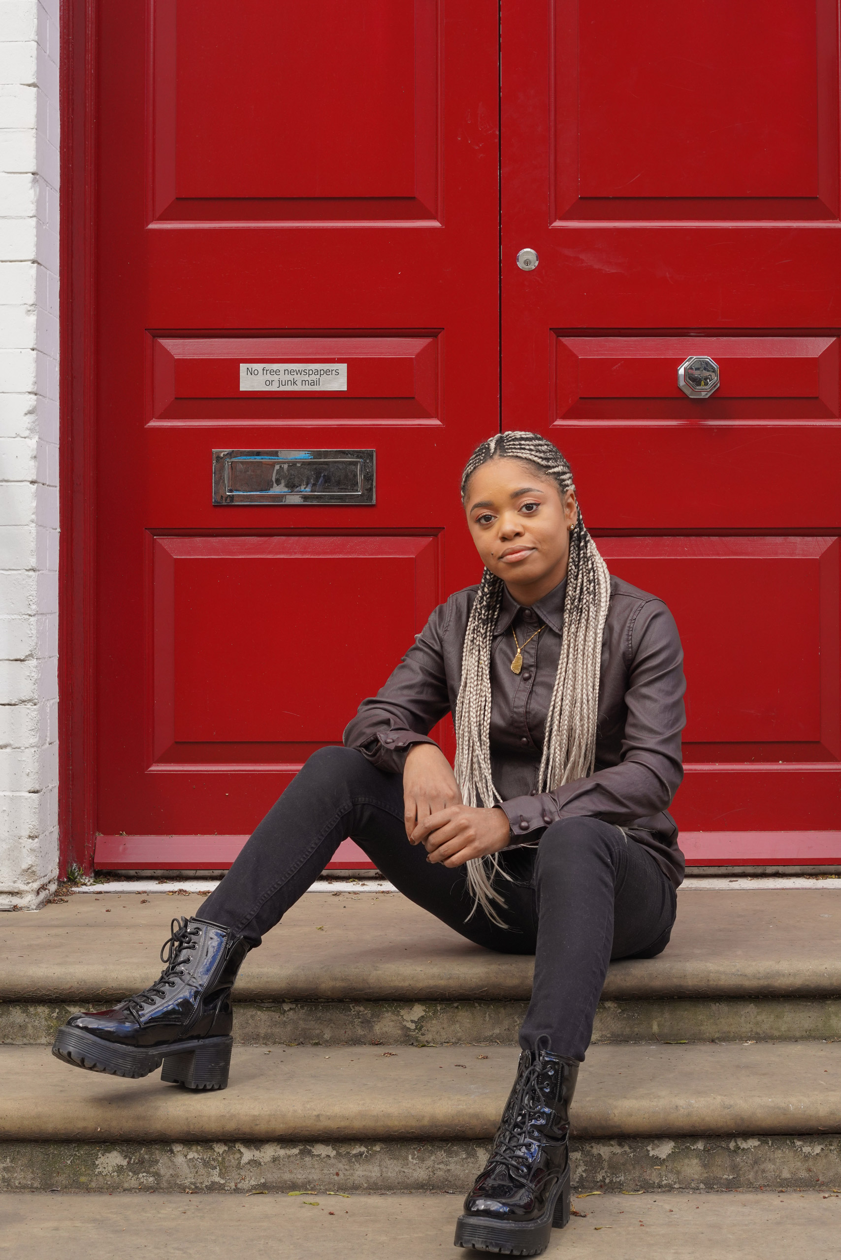 Lauren Marie Haywood looking at the camera in front of a red panelled door