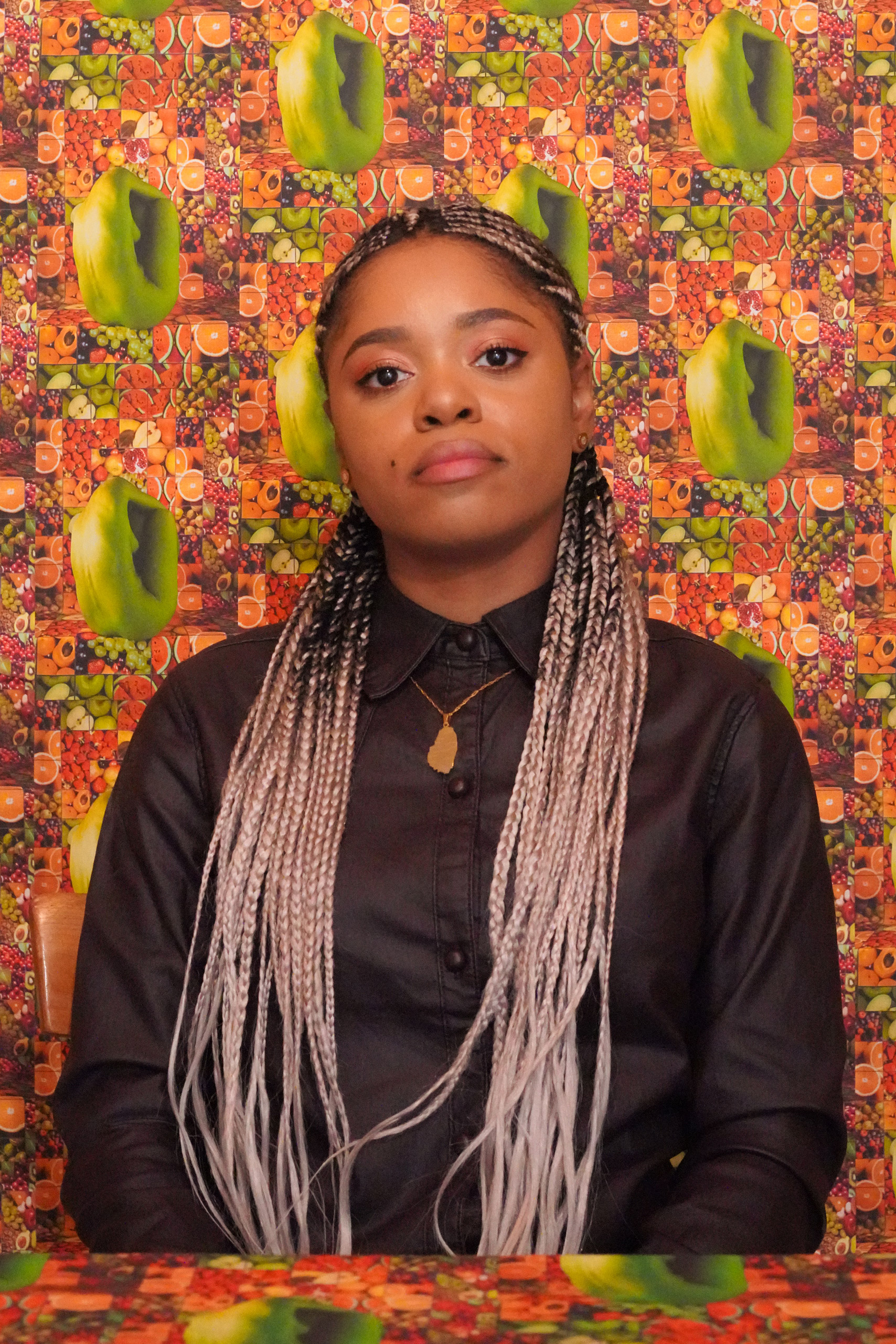 Lauren Marie Haywood looking at the camera while sitting in a room with brightly coloured fruit wallpaper