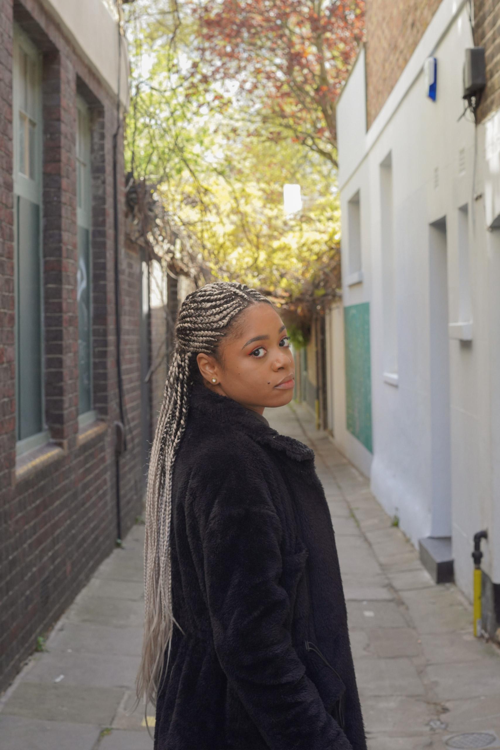 Lauren Marie Haywood in an sunny alleyway looking at the camera